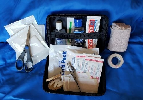 Advanced car camping first aid kit, Gauze, scissors, ace wrap, tape and other first aid items. Black kit on a blue background.