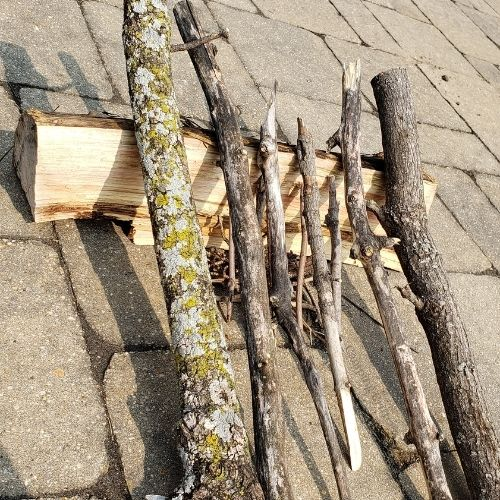 Example of Lean-to campfire. A large log lays on it's side with smaller sticks leaned between the log and the ground. The space below the sticks has small tinder.