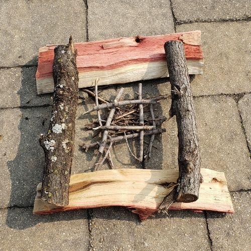 Example of log cabin campfire. Sticks and logs arranged in a square with smaller sticks in the middle.