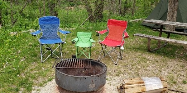 green toddler camp chair next to blue and red adult camp chairs near fire pit