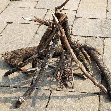 Example of a teepee campfire. Larger sticks balanced against each other so they stand up forming a pyramid or teepee shape. The space in the middle is filled with tinder.