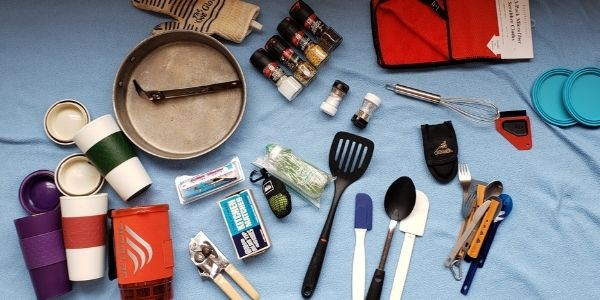 Packing for cooking at camp. Mugs, stove, spatula, spoons, spices, multitool, whisk, Ove Glove, dish towel, collapsible bowls, can opener, dish soap.