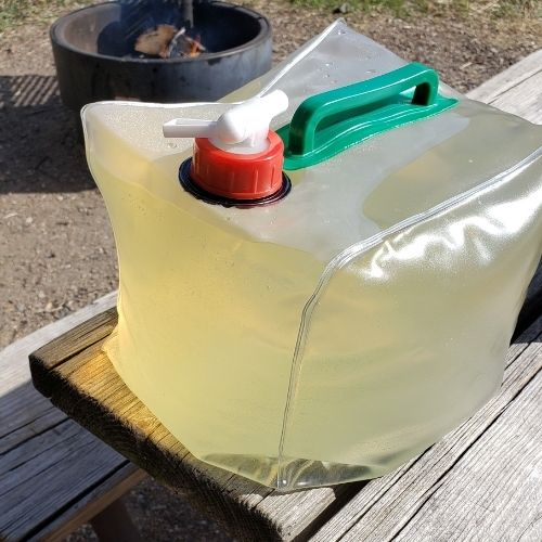 Collapsible water jug with campground water in it, slightly yellow