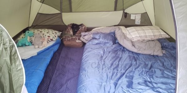 Tent with queen air mattress and twin air mattress, double sleeping bag and single sleeping bag. Duffle bag packed with clothes