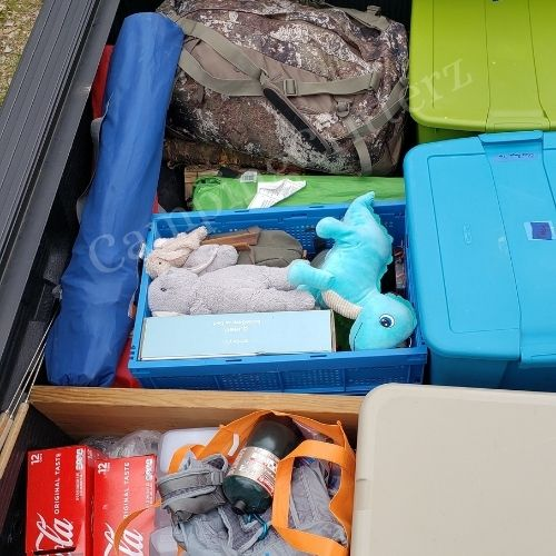 Truck packed with camping gear. Blue and green tote bins, camo duffel bag, camping chairs, propane cannister, drinks, cooler, air mattress in box and stuffed animals