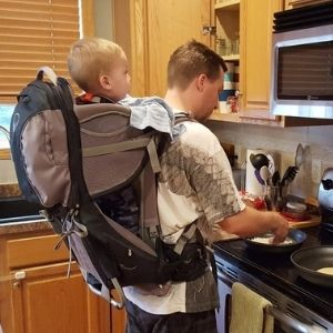 Dad cooking breakfast with a child in an Osprey backpack child carrier