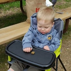 Infant in camping highchair eating a snack