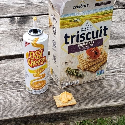 Crackers with spray cheese on a camping picnic table