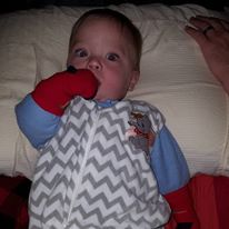 Baby in tent, wearing sleep sack and socks as mittens