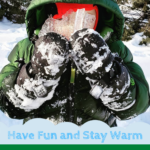child holding up piece of ice while winter camping